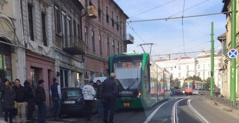 O maşină care bloca circulaţia tramvaielor, luată pe sus de călători